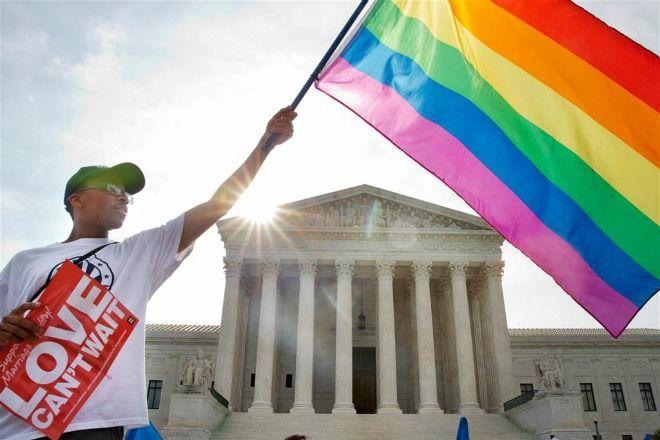 Một người da đen đang giương cao ngọn cờ LGBT